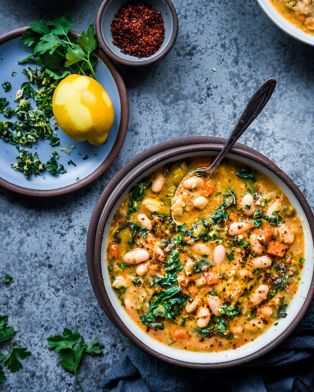 bowl of white bean soup with kale and gremolata in bowl with spoon and gremolata on side