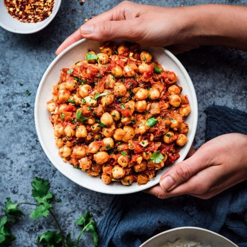 bowl of Indian chana masala framed by hands