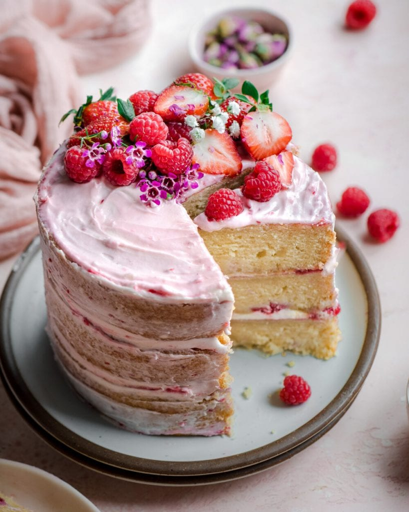 raspberry vanilla layer cake on plate with berry topping