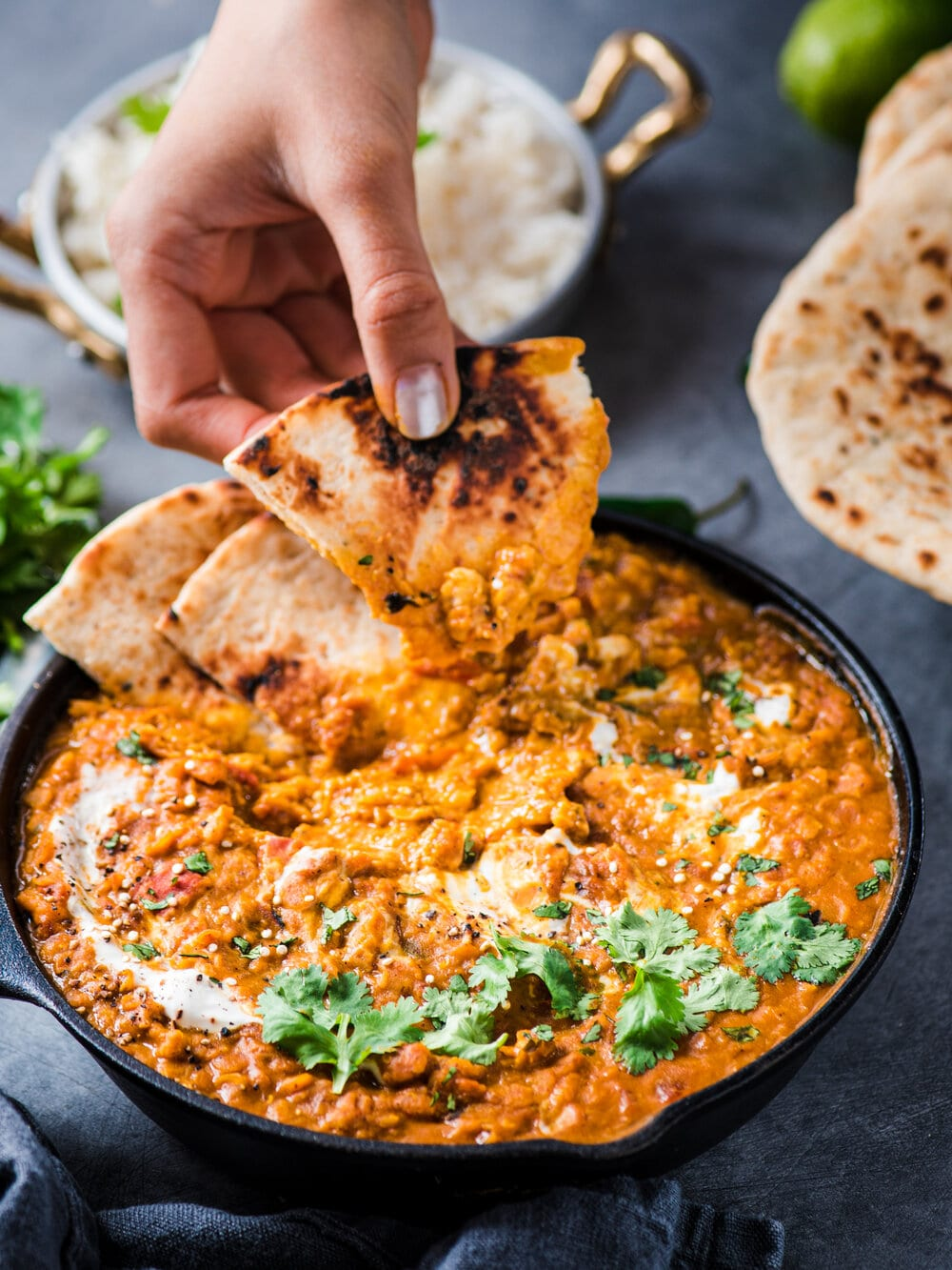 hand dipping naan bread into red lentil curry