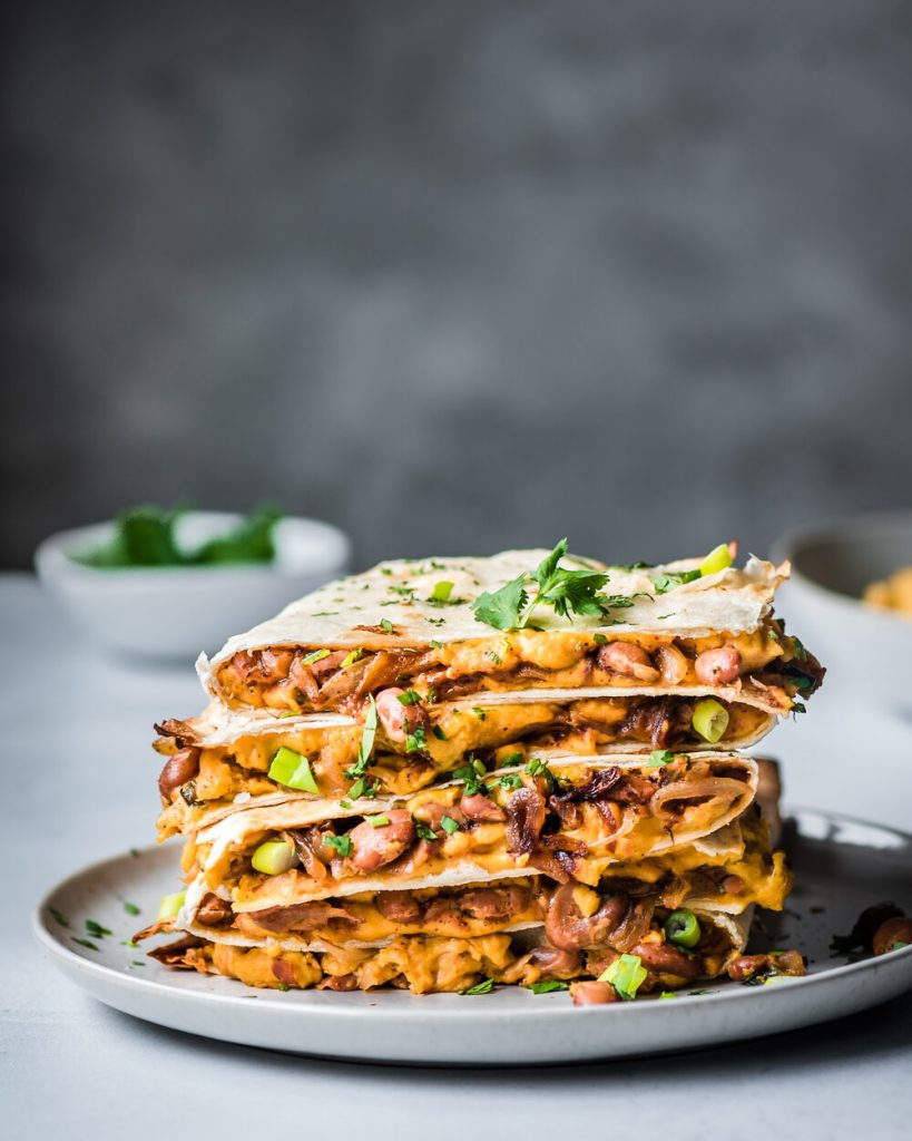 refried beans and vegan cheese quesadillas stacked on a plate