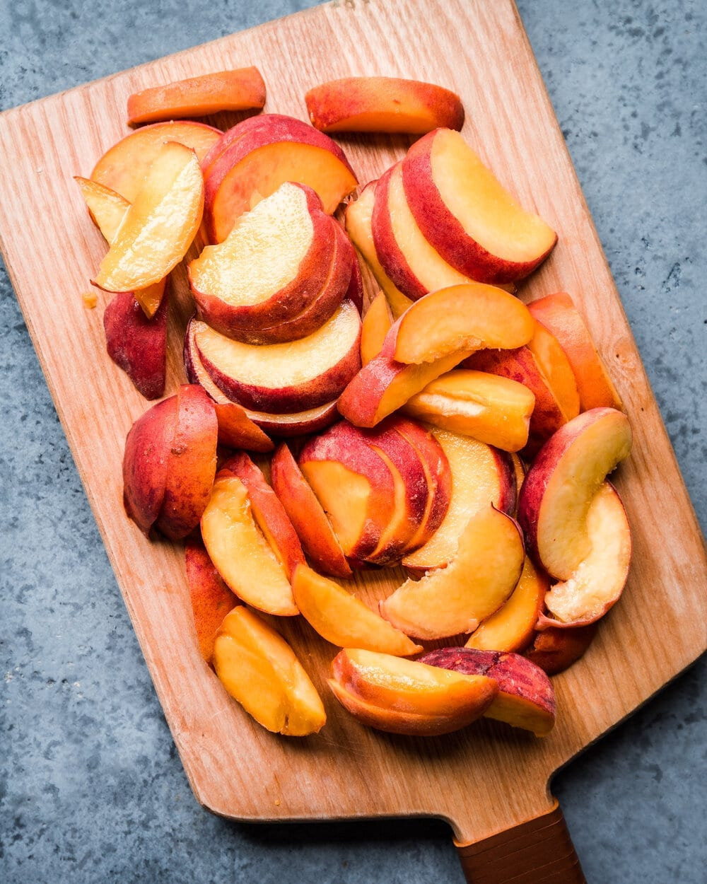 sliced peaches on wooden cutting board