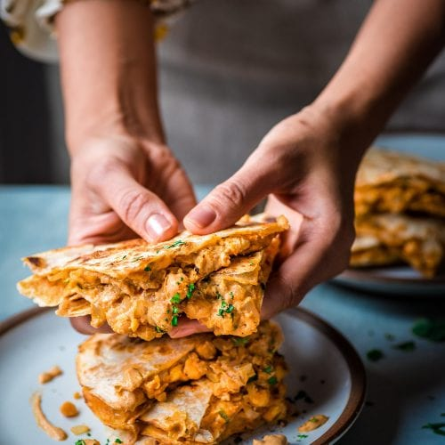 moody close up shot of buffalo chickpea quesadillas on a plate being picked up by woman's hands
