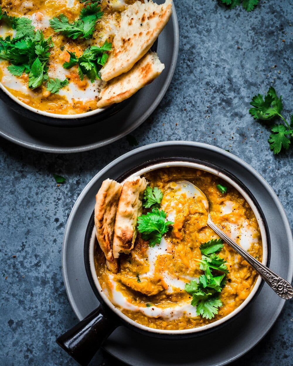 two bowls of Indian red lentil sweet potato soup with naan