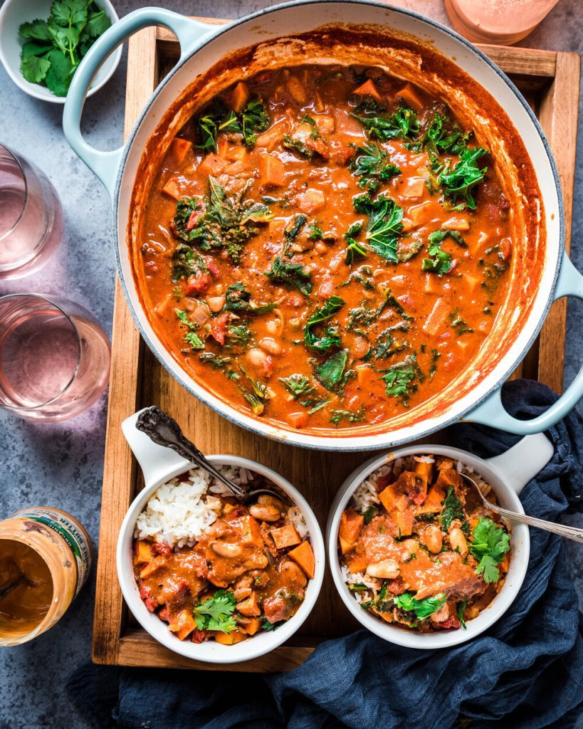 vegan west african peanut stew in dutch oven with two small bowls of peanut stew