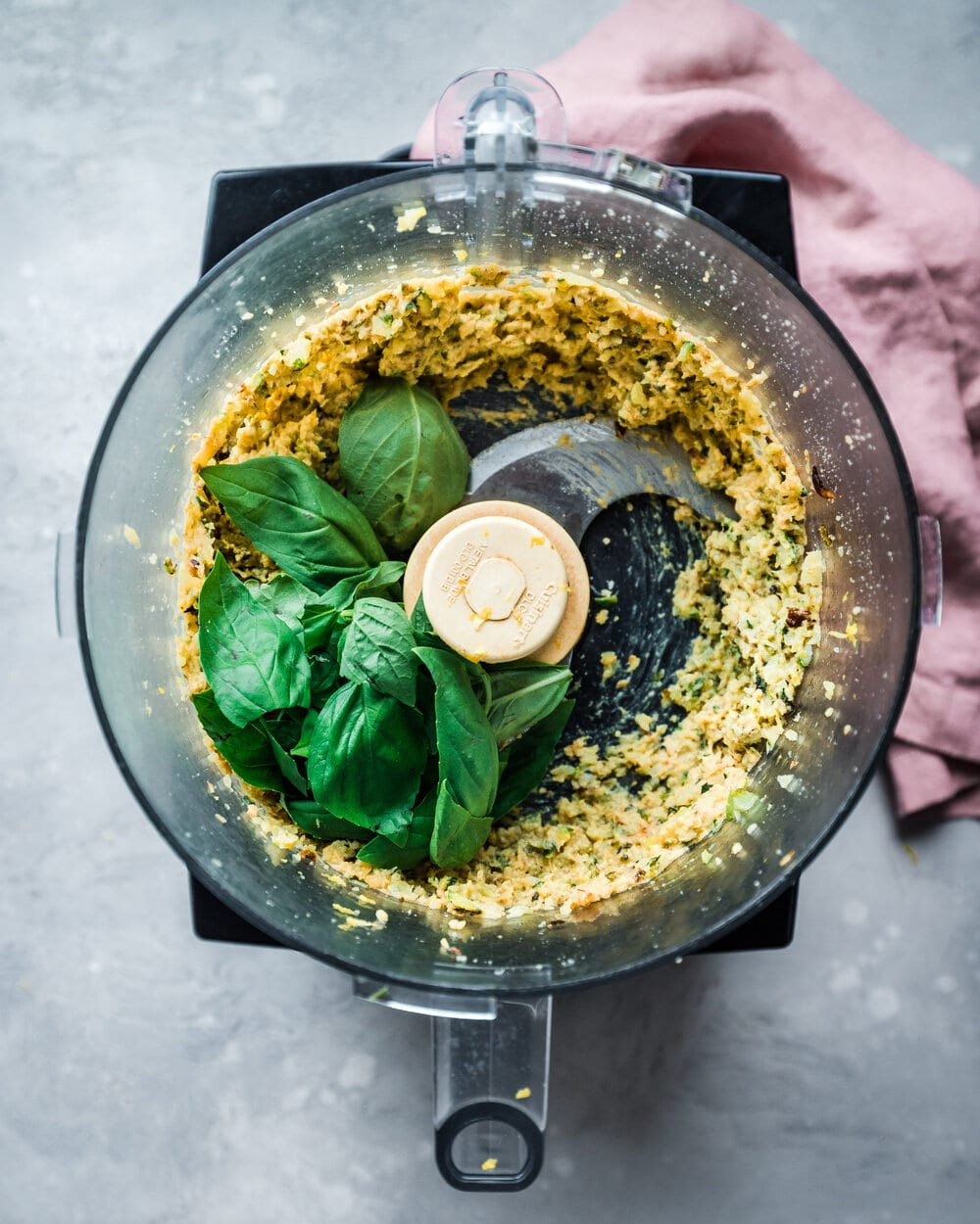 Spinach being added to pine nuts in food processor