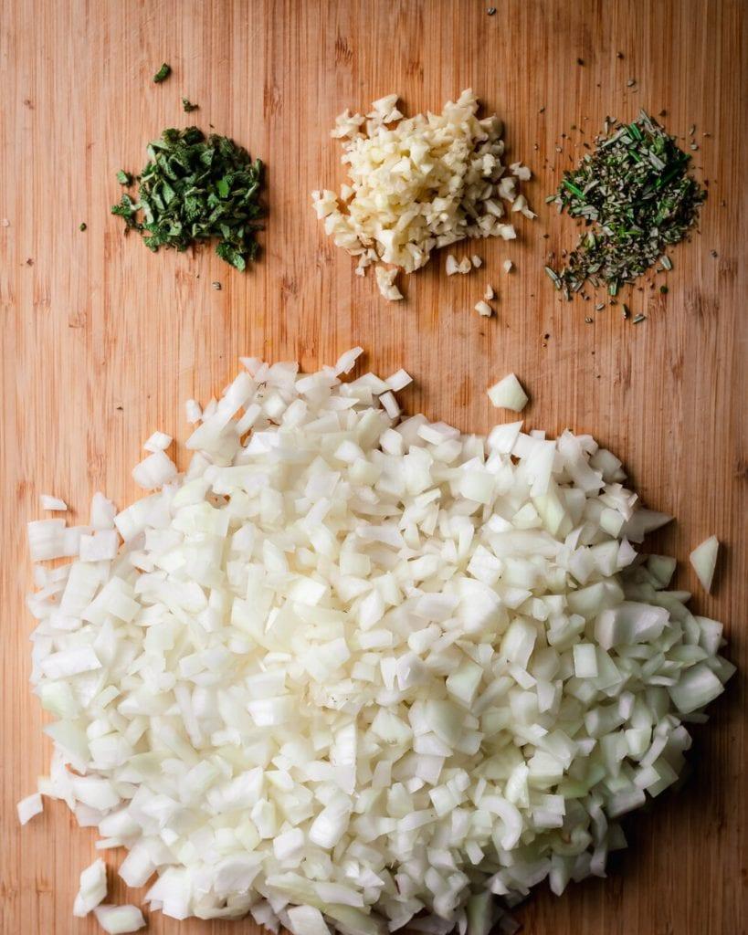 raw onion, garlic, rosemary and sage on cutting board