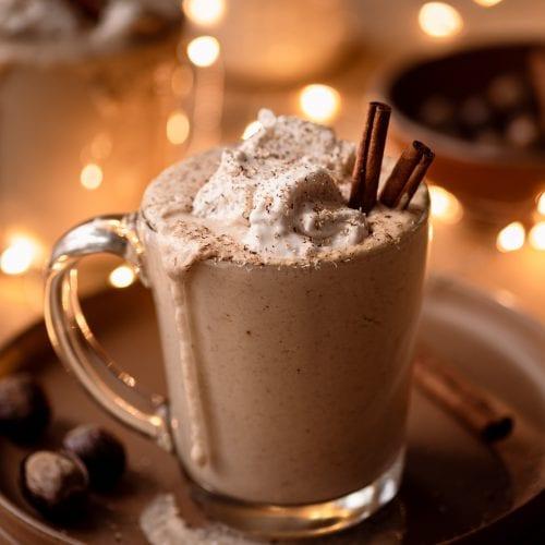 creamy vegan spiced eggnog in glass mug with holiday lights