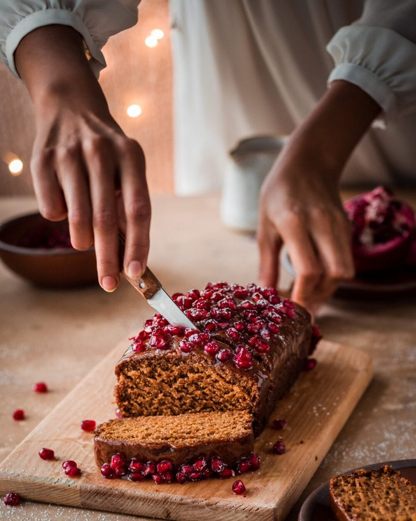 woman slicing gingerbread cake with pomegranate seeds with holiday scene