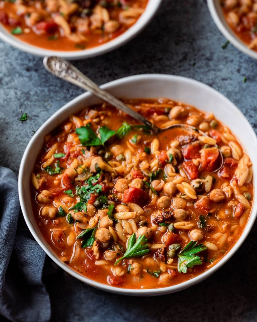 tomato orzo chickpea soup in bowl with spoon