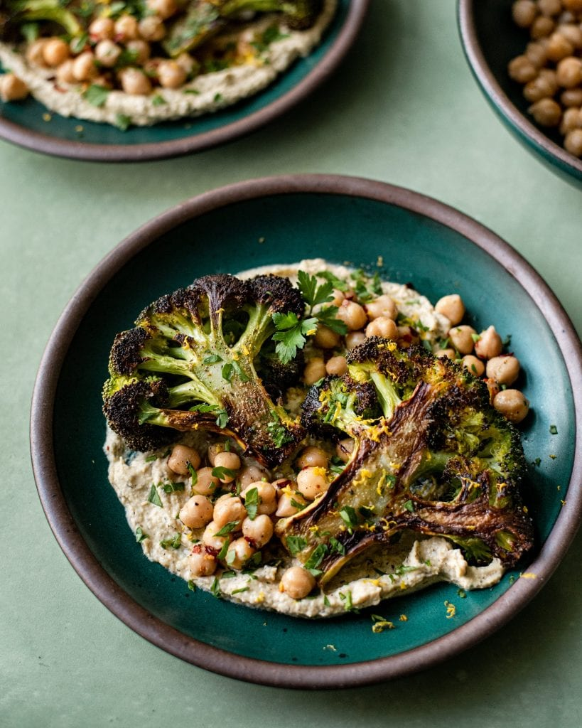 Veganuary Tips. roasted broccoli steak with chickpeas on top of hummus