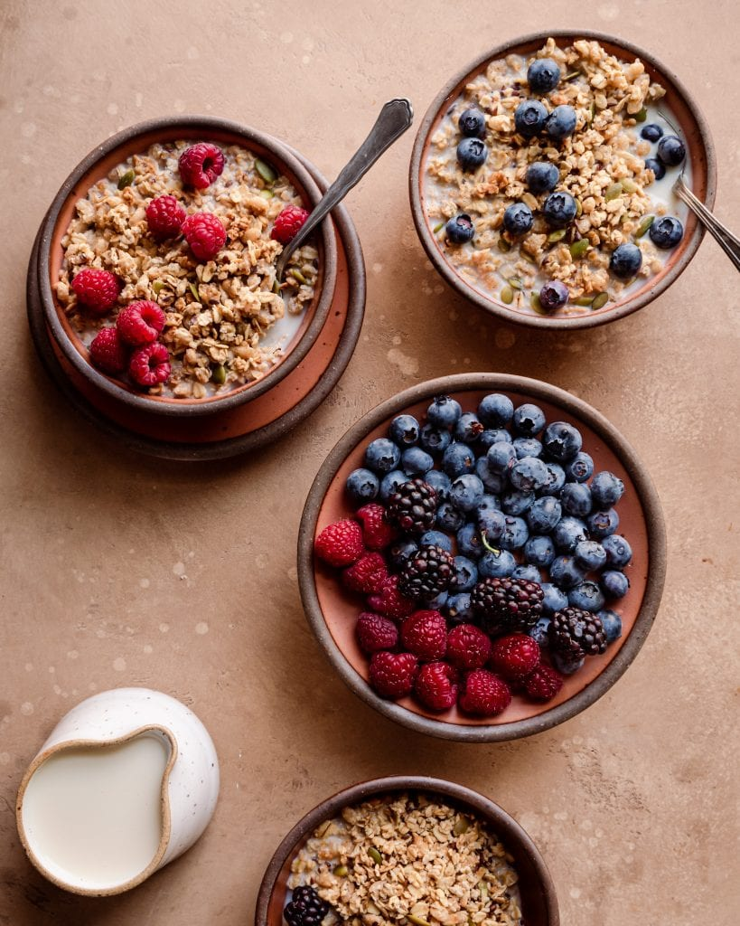 Veganuary Tips. bowls of granola with milk and berries on brown board