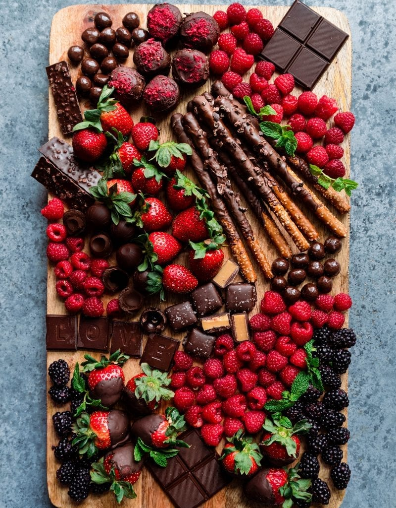 dessert board with berries, chocolates, and snacks