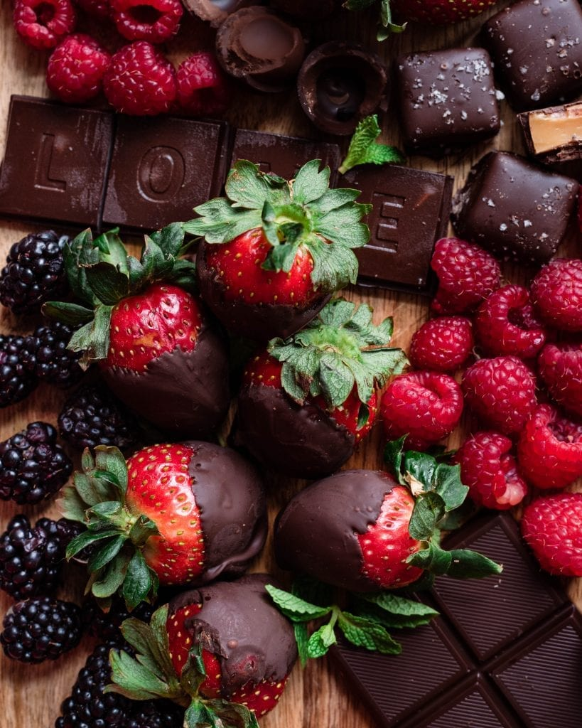 chocolate covered strawberries on board with other candies