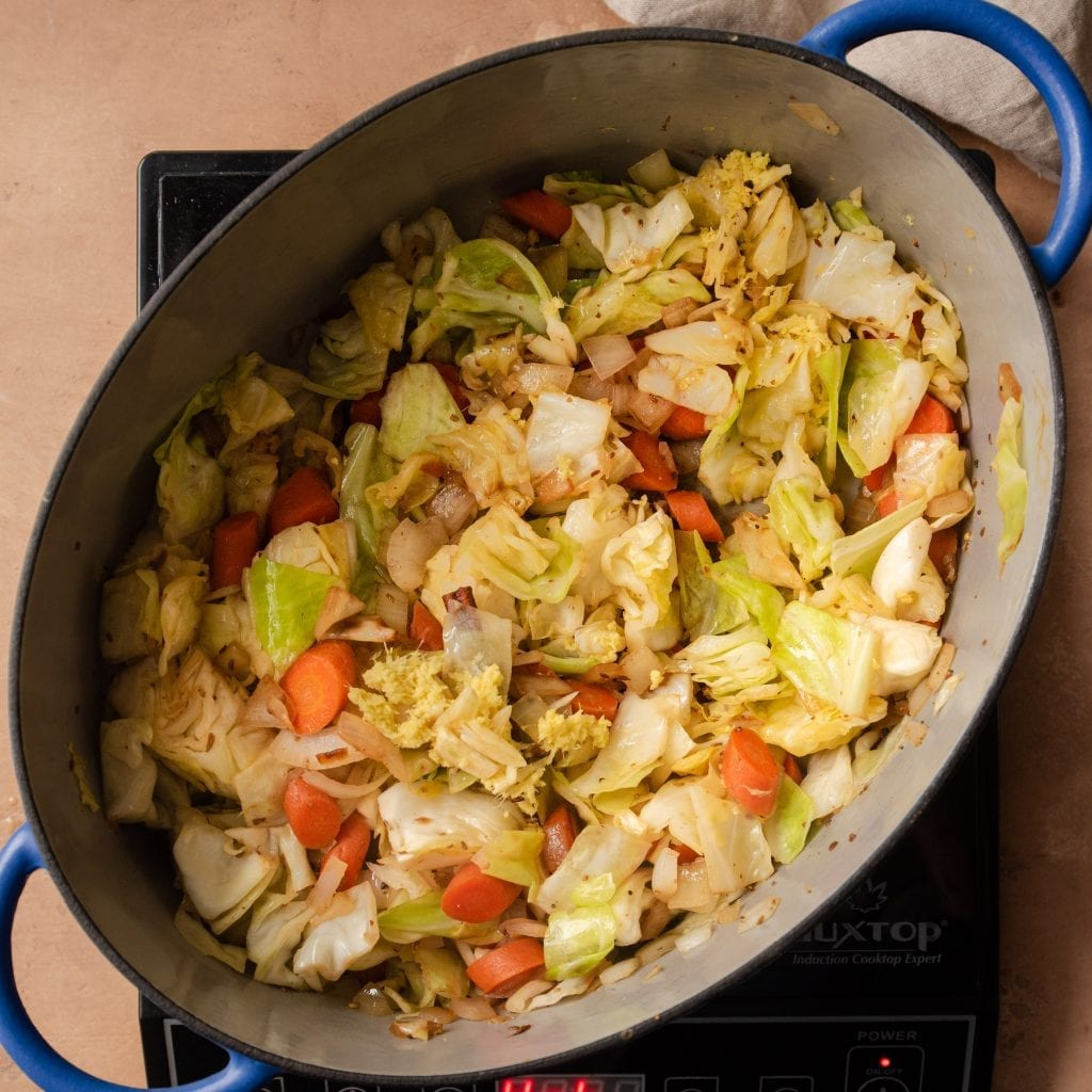 sauted cabbage and carrots with ginger and garlic in a dutch oven
