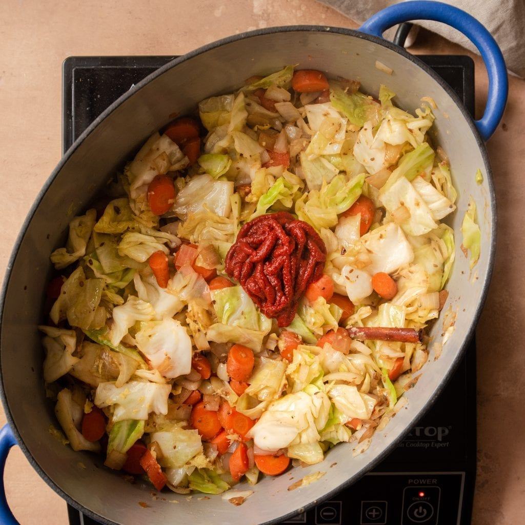 tomato paste on top of cabbage and carrots in dutch oven
