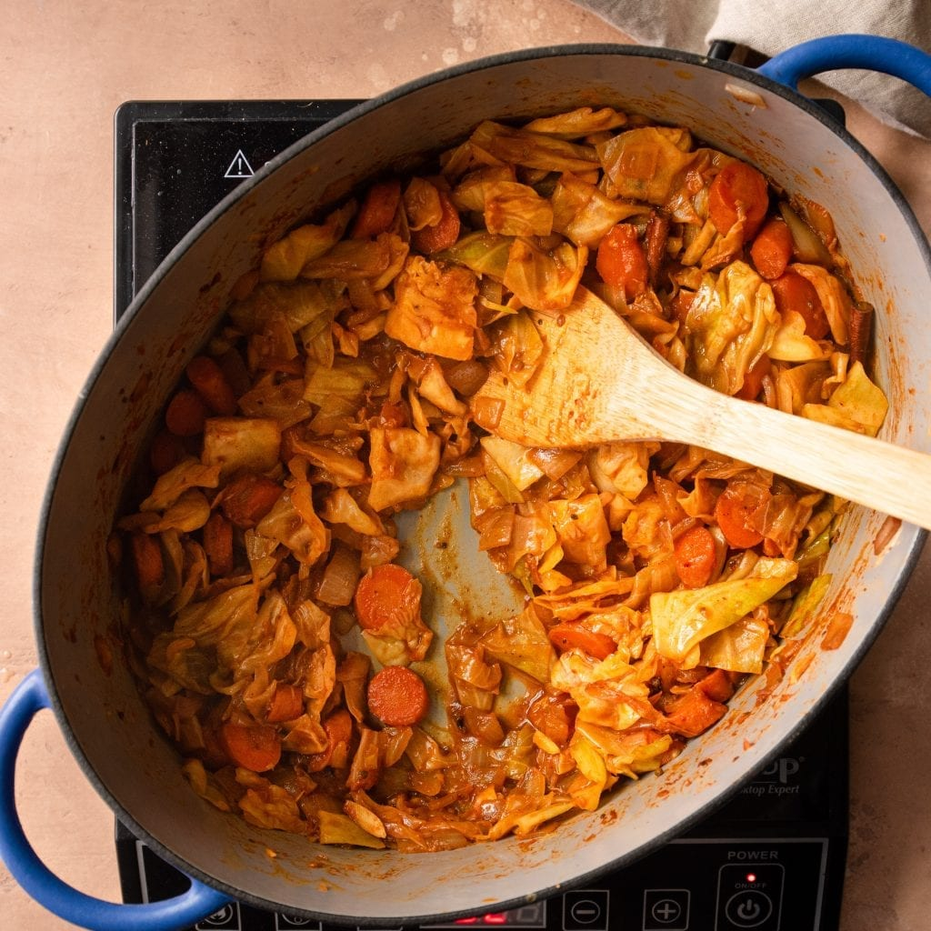 cooked cabbage and carrots and tomato paste in dutch oven