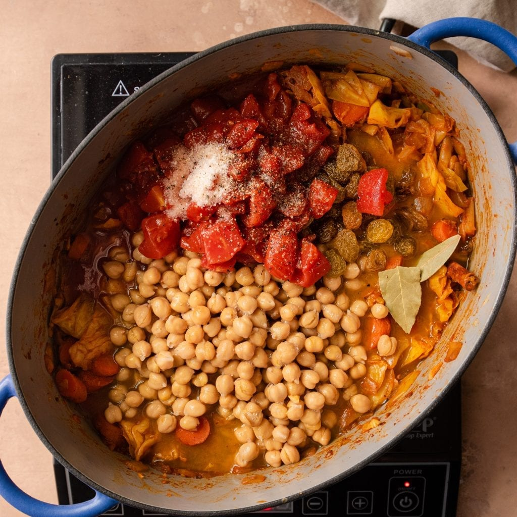 chickpeas and tomatoes in a stew in a dutch oven