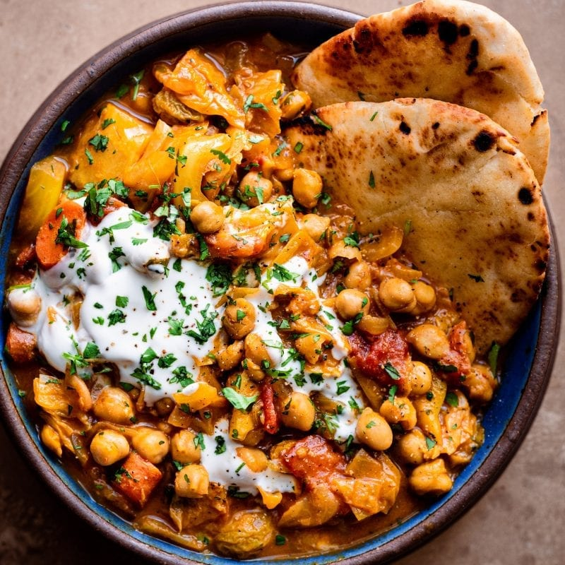 bowl of indian chickpea stew with yogurt and naan