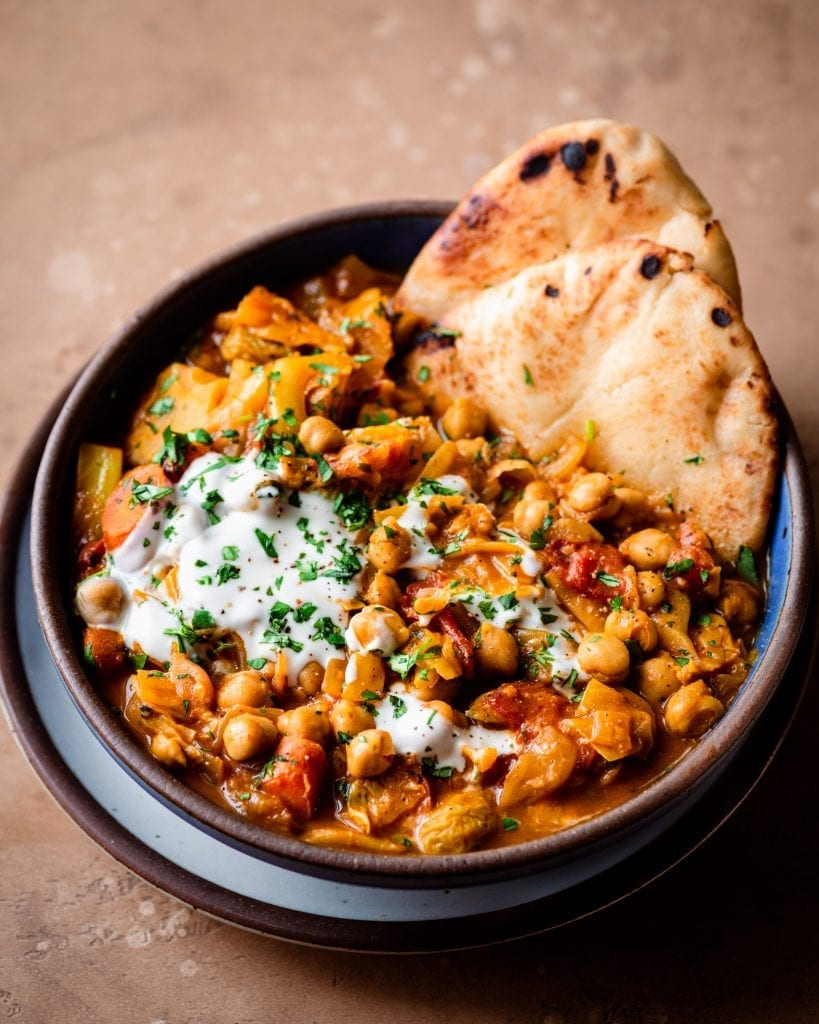 indian chickpea stew in a bowl with naan and yogurt