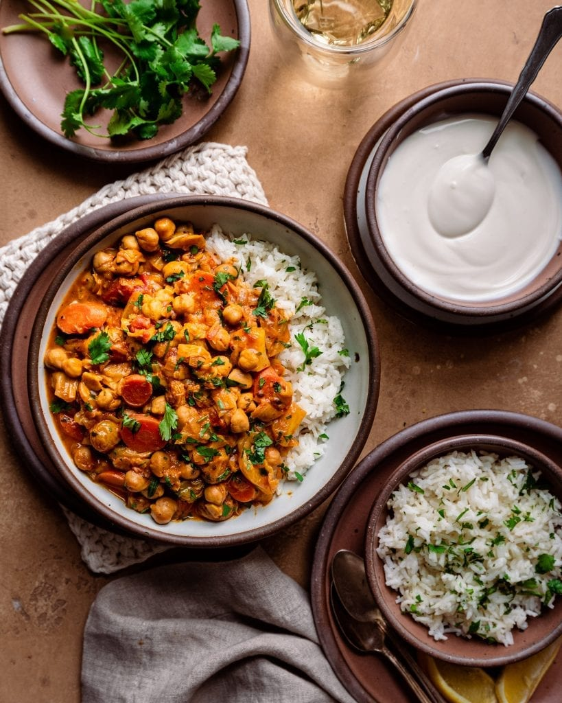 dinner scene with indian chickpea stew, rice, yogurt, and cilantro