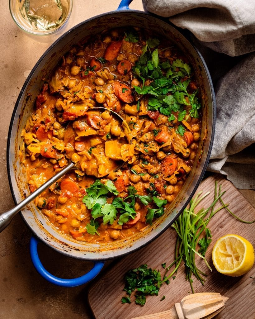dutch oven with ladle of chickpea stew and cutting board with garnishes