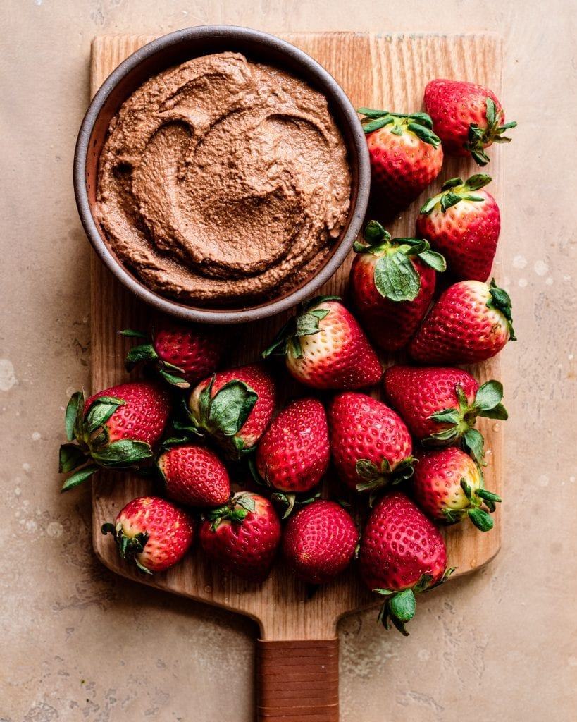 cutting board with strawberries and chocolate hummus dip
