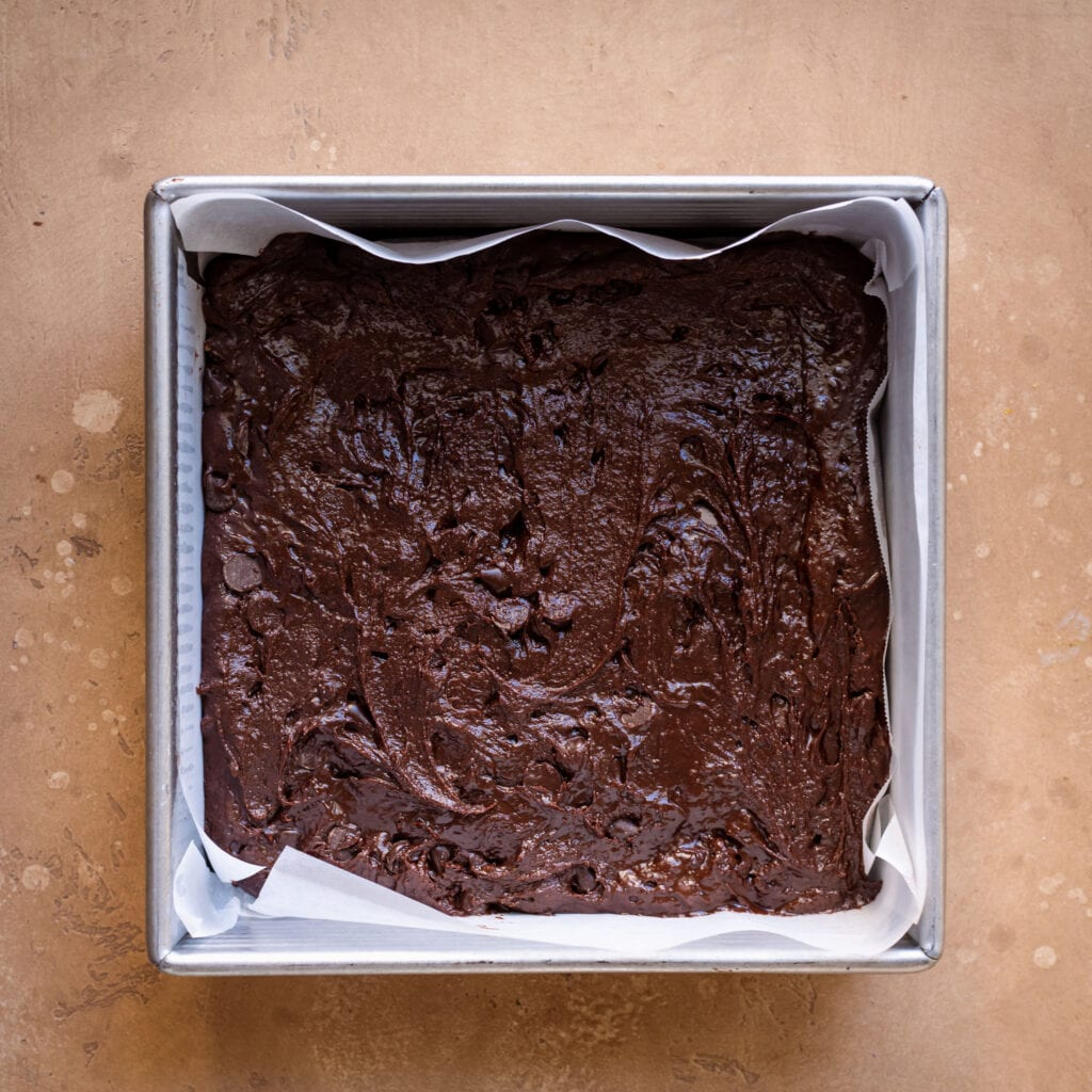 brownie batter in 8x8 baking pan lined with parchment paper