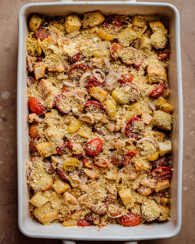 baked tomato casserole in baking pan with cashew parmesan on top