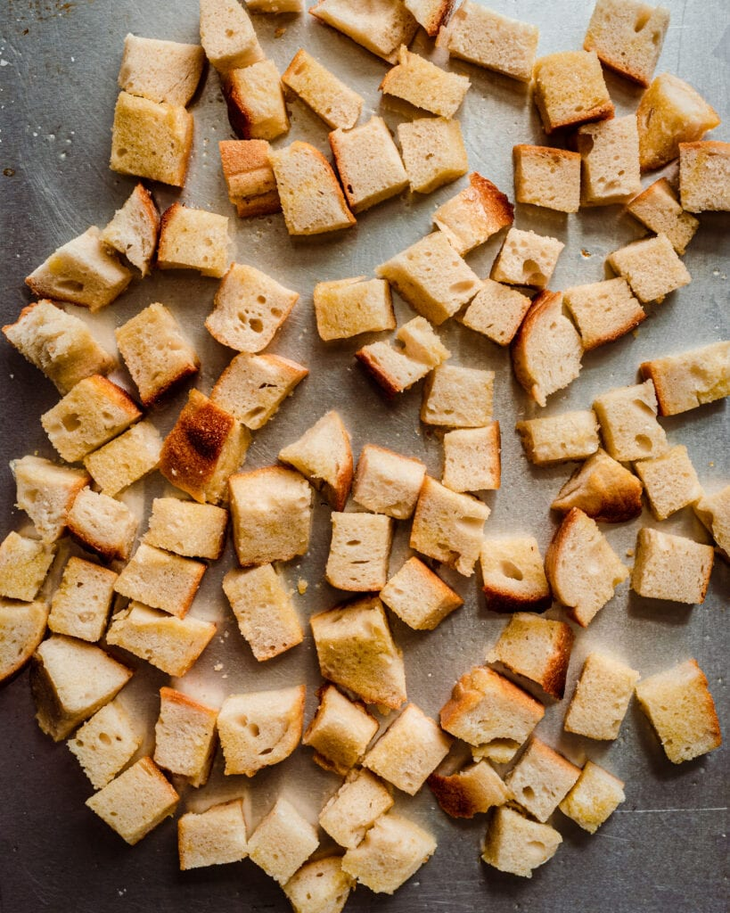 bread cubes tossed with olive oil on sheet pan