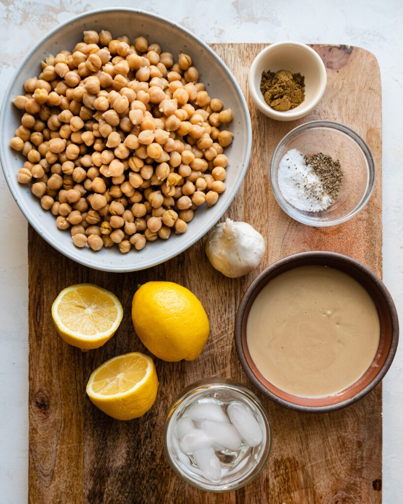 chickpeas, tahini, lemons, garlic on cutting board - ingredients for hummus