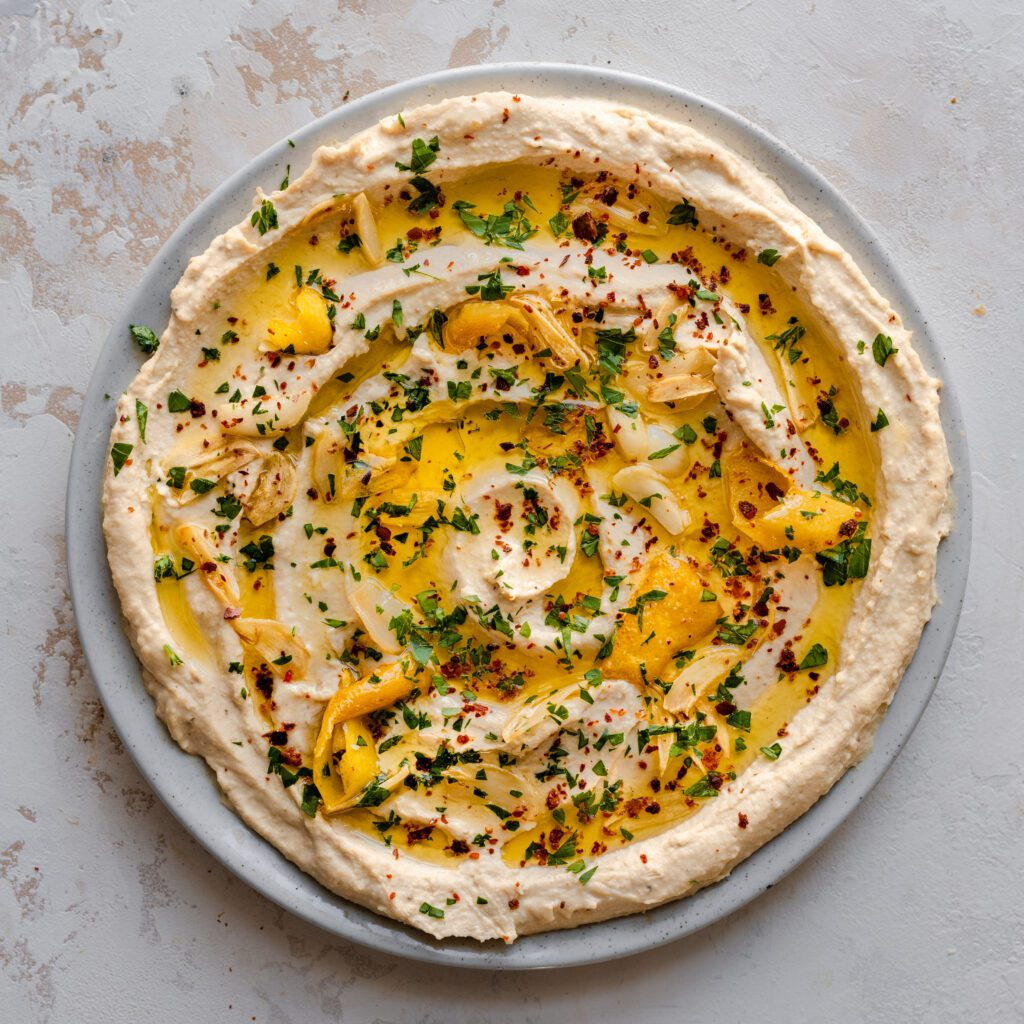 creamy hummus swirled on plate with olive oil, parsley, lemon, and paprika on top