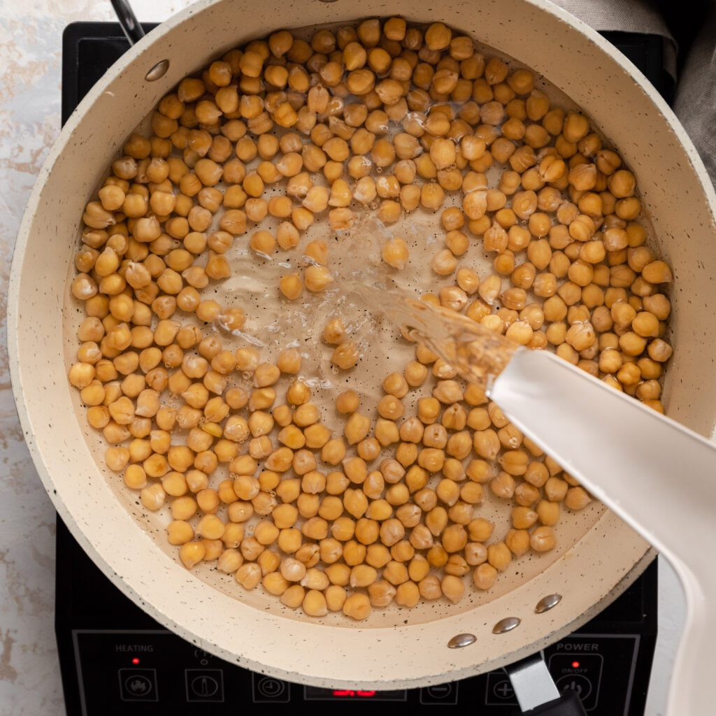 pouring water into saucepan of chickpeas