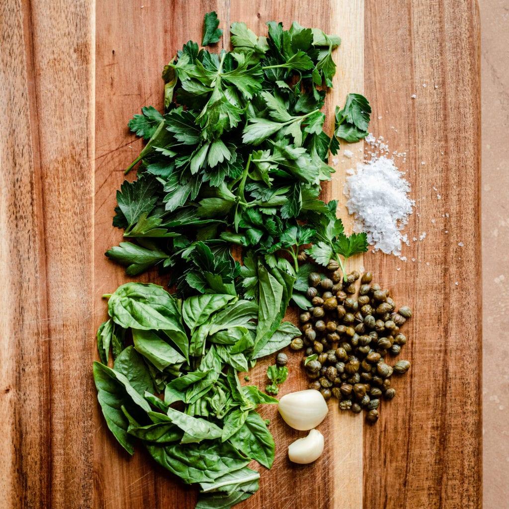 parsley basil capers garlic salt on cutting board for gremolata