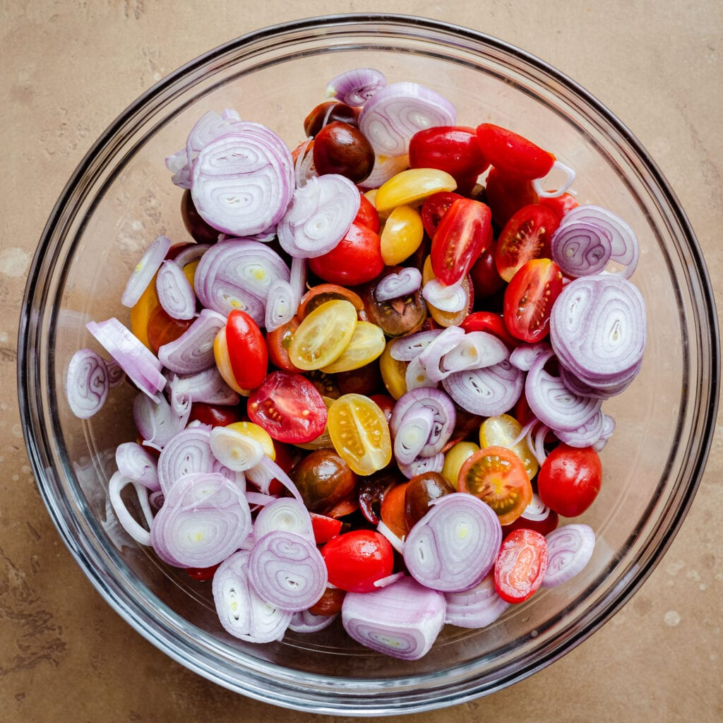 sliced shallots and cherry tomatoes in bowl