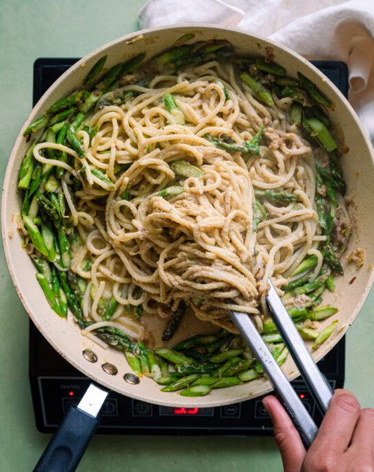tossing spaghetti with tongs in a saute pan with asparagus