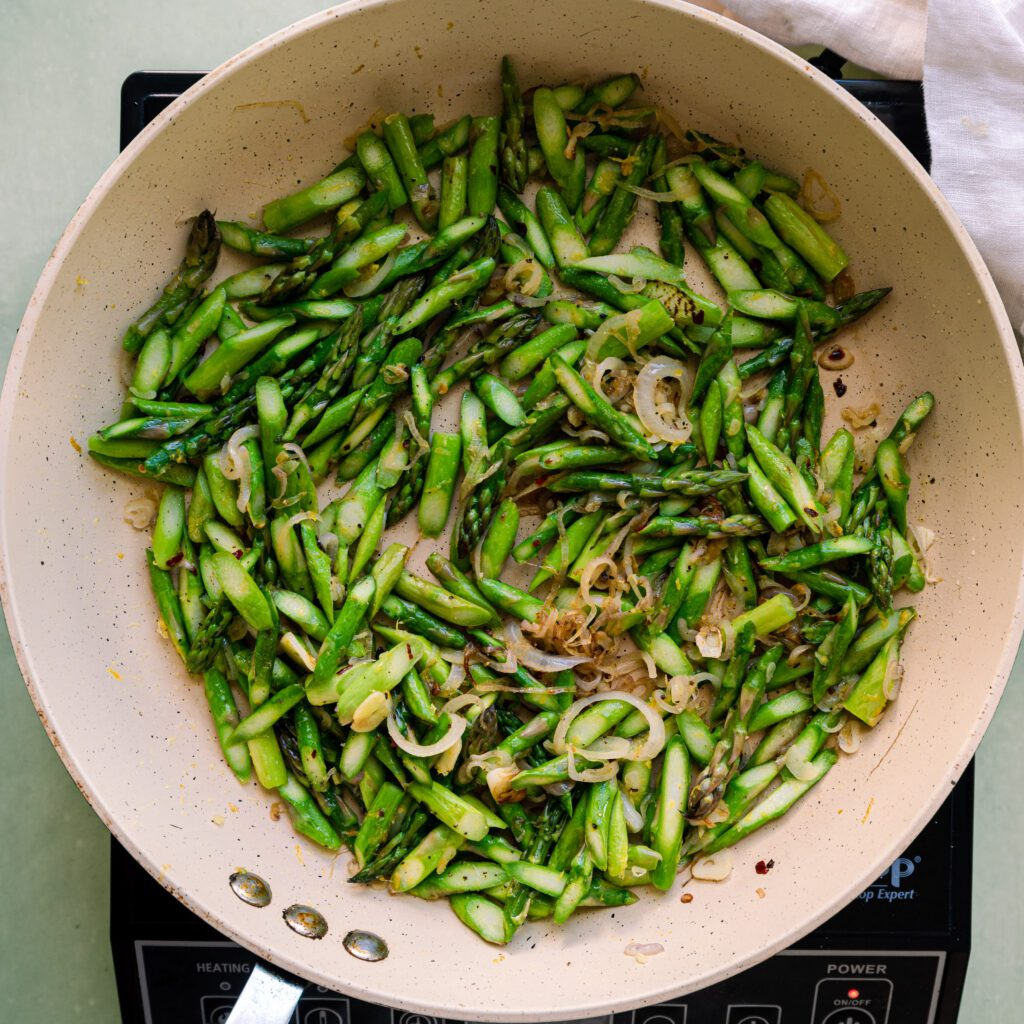 sauteed asparagus and shallots in a frying pan