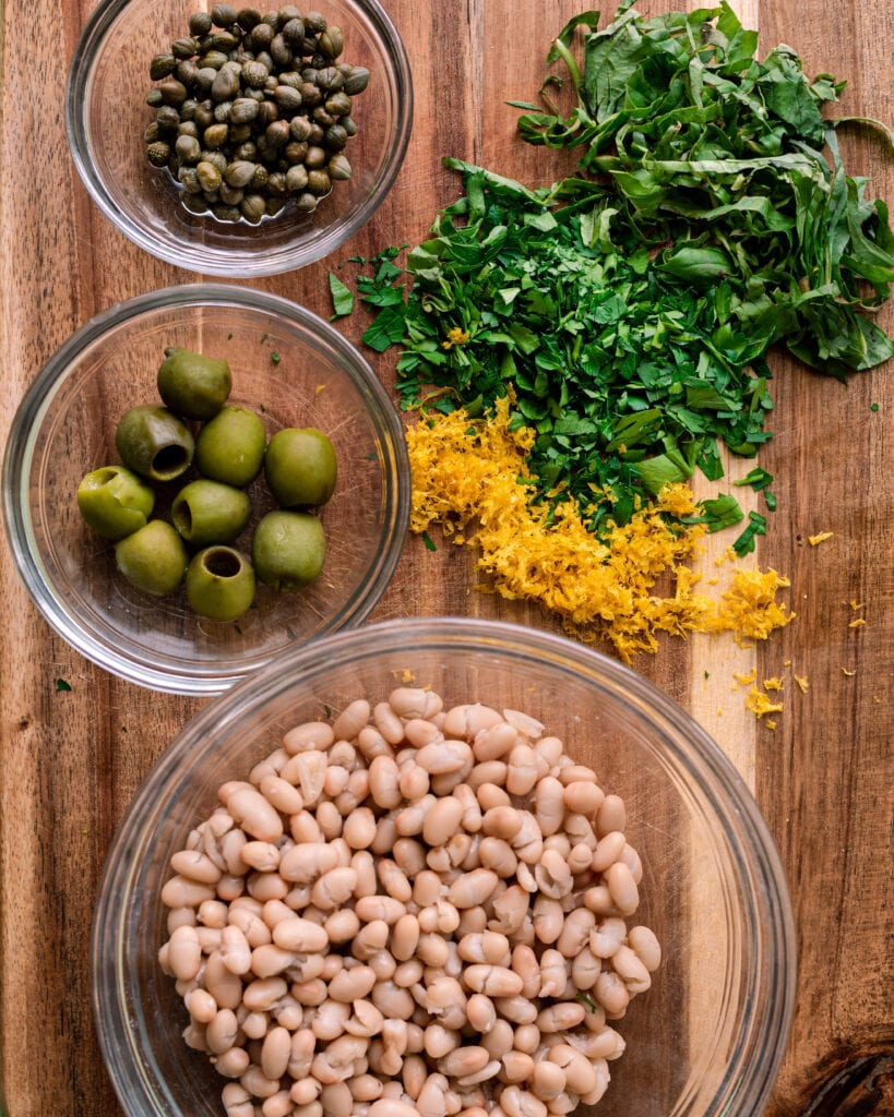 chopped herbs, lemon zest, olives, capers, and beans on cutting board