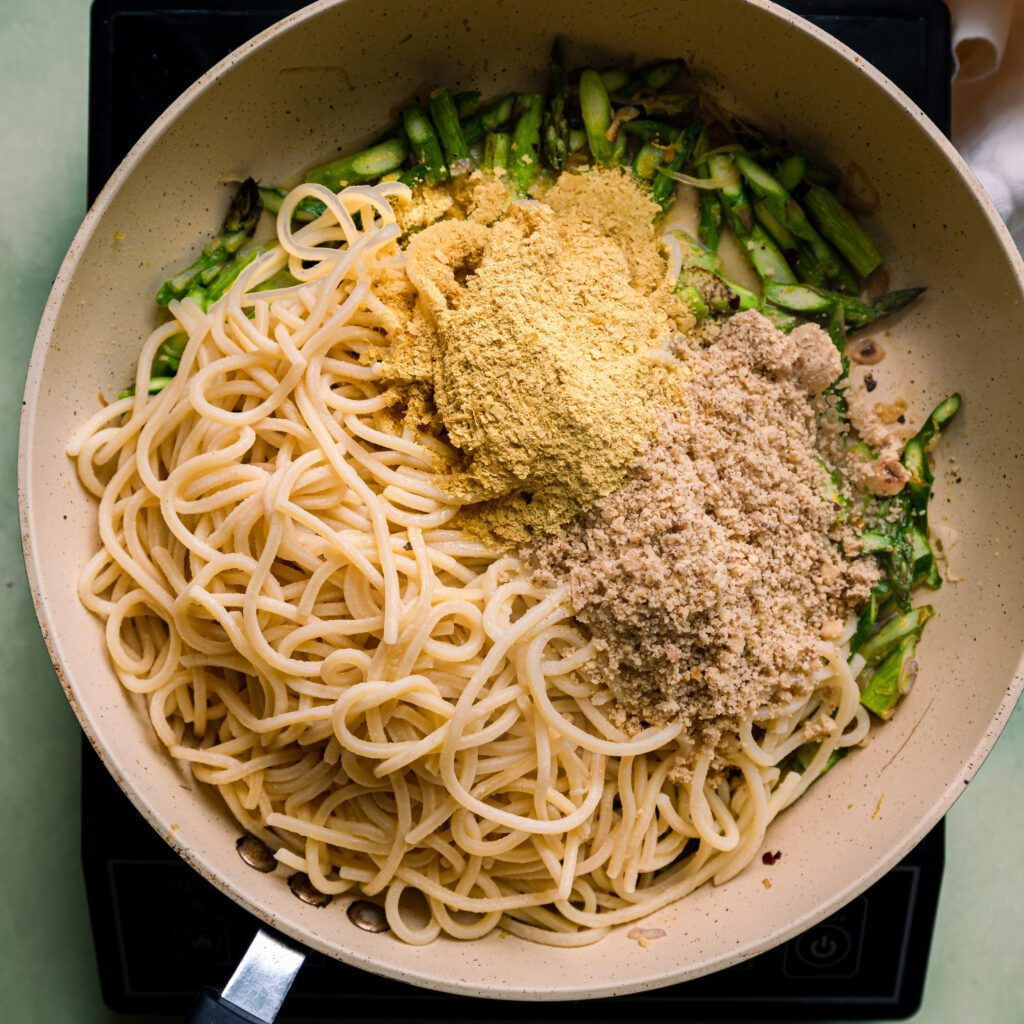 spaghetti and asparagus in saute pan with nutritional yeast and crushed walnuts