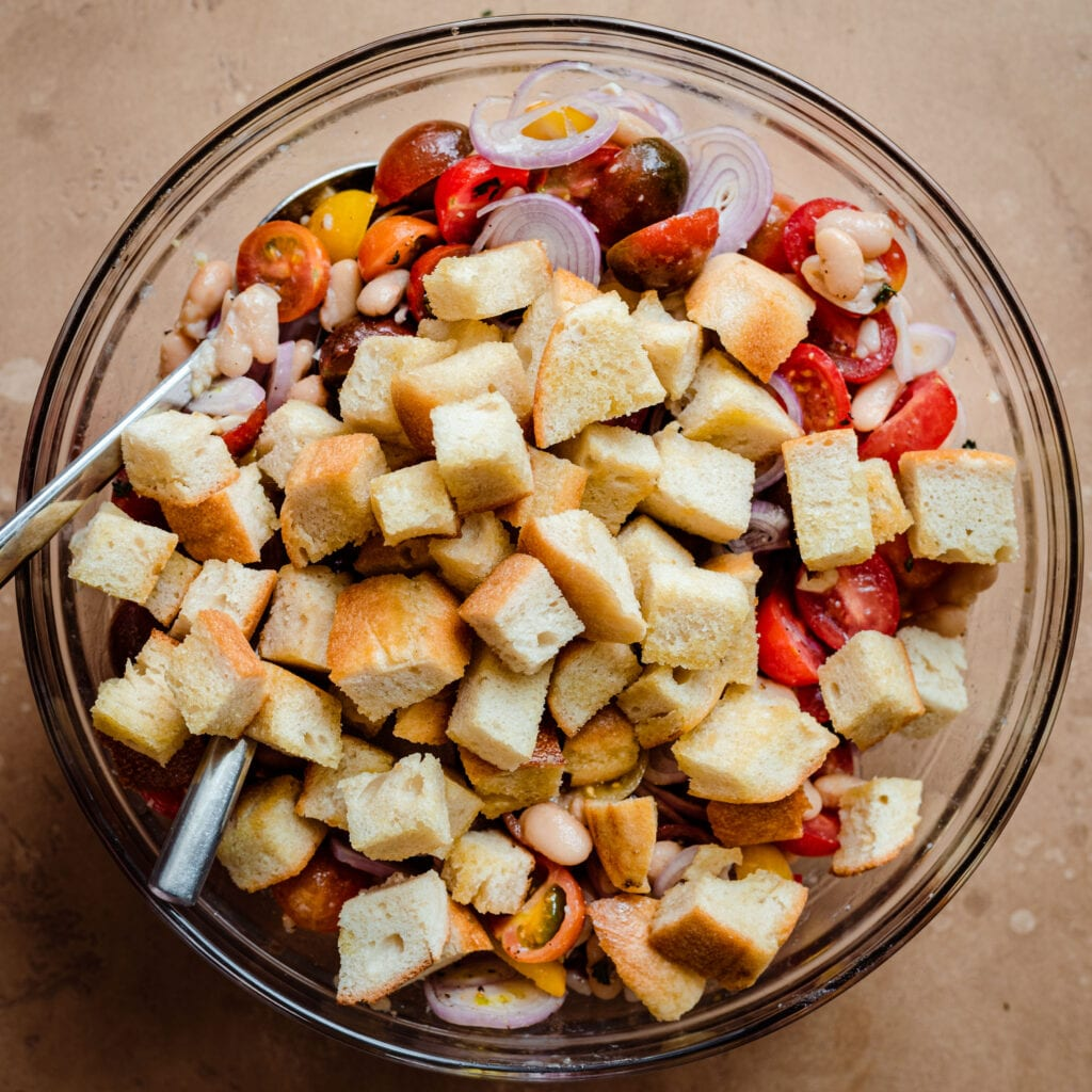 toasted bread cubes on top of tomatoes in bowl