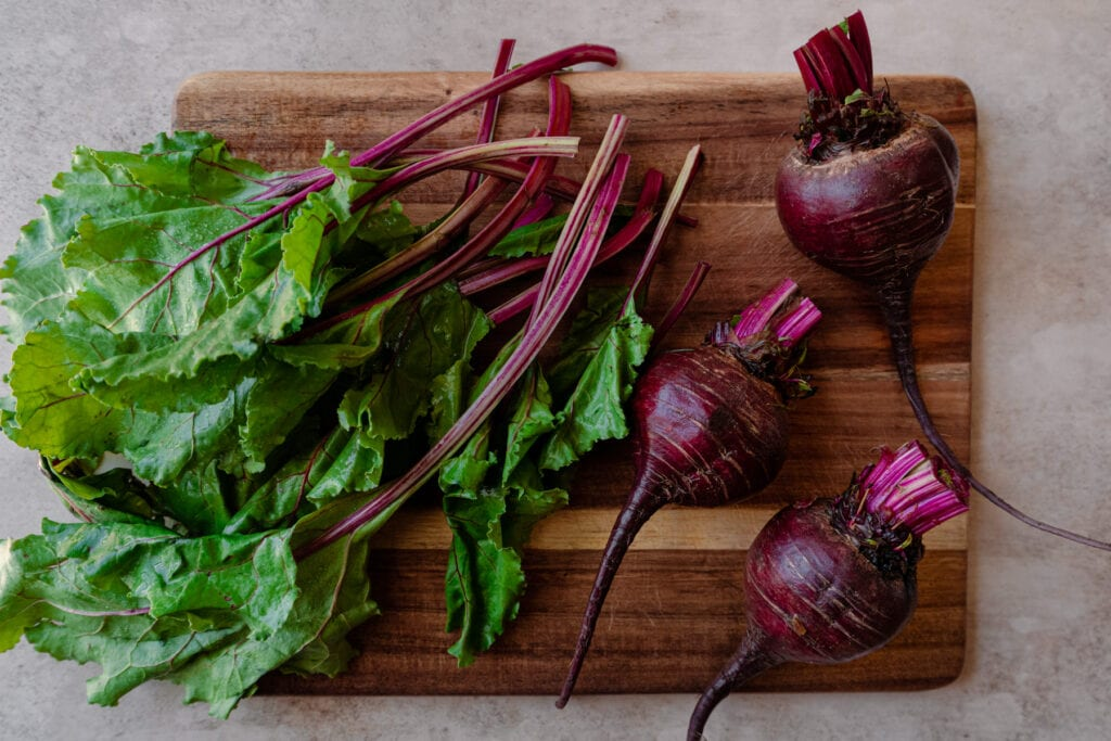 bunch of beets sliced off with beet greens on wooden cutting board