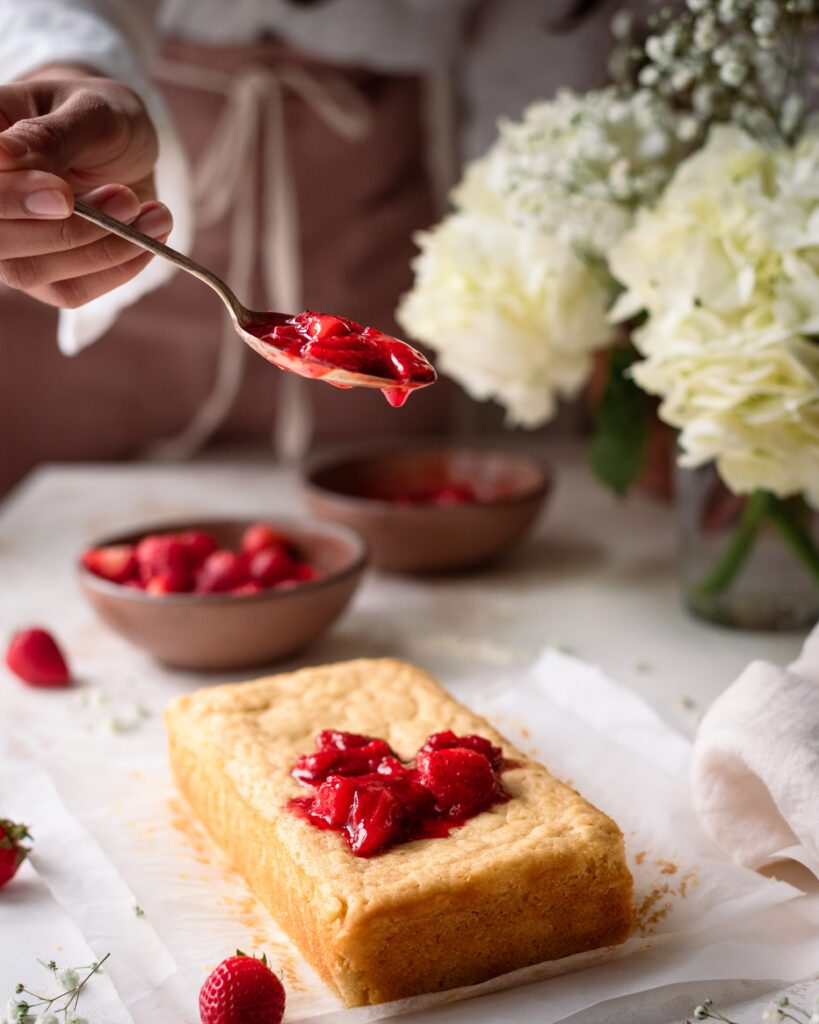 woman spooning strawberry sauce onto lemon olive oil cake in romantic food photography scene