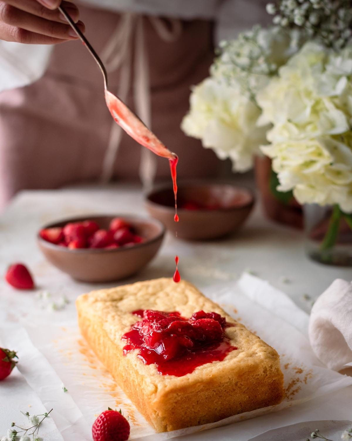 woman drizzling strawberry sauce onto lemon olive oil cake in romantic food photography scene