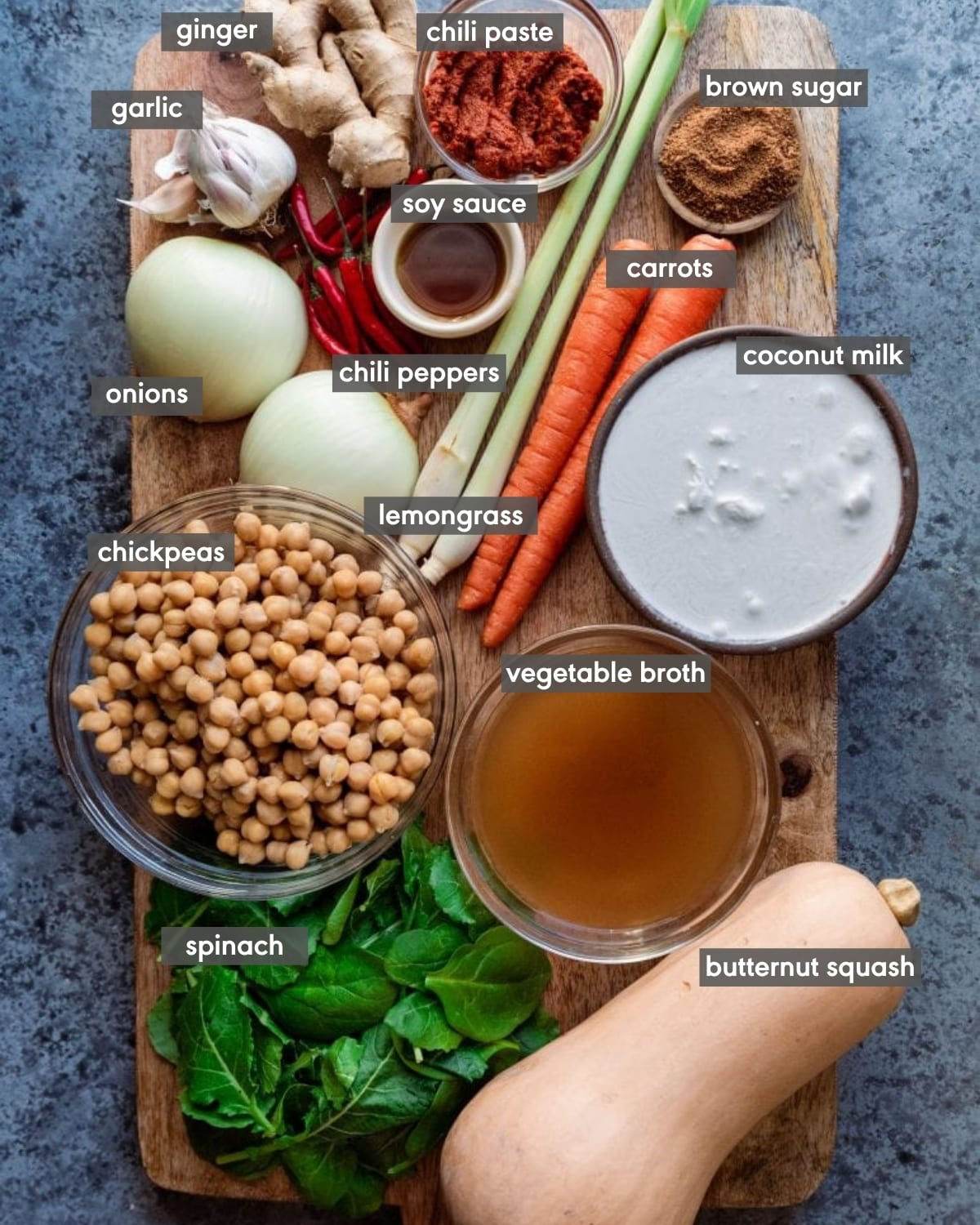 ingredients on cutting board with butternut squash, chickpeas, lemongrass, coconut milk, soy sauce, bird's eye chili peppers, spinach, soy sauce, brown sugar, chili paste, vegetable broth, coconut milk, garlic, ginger, and onions