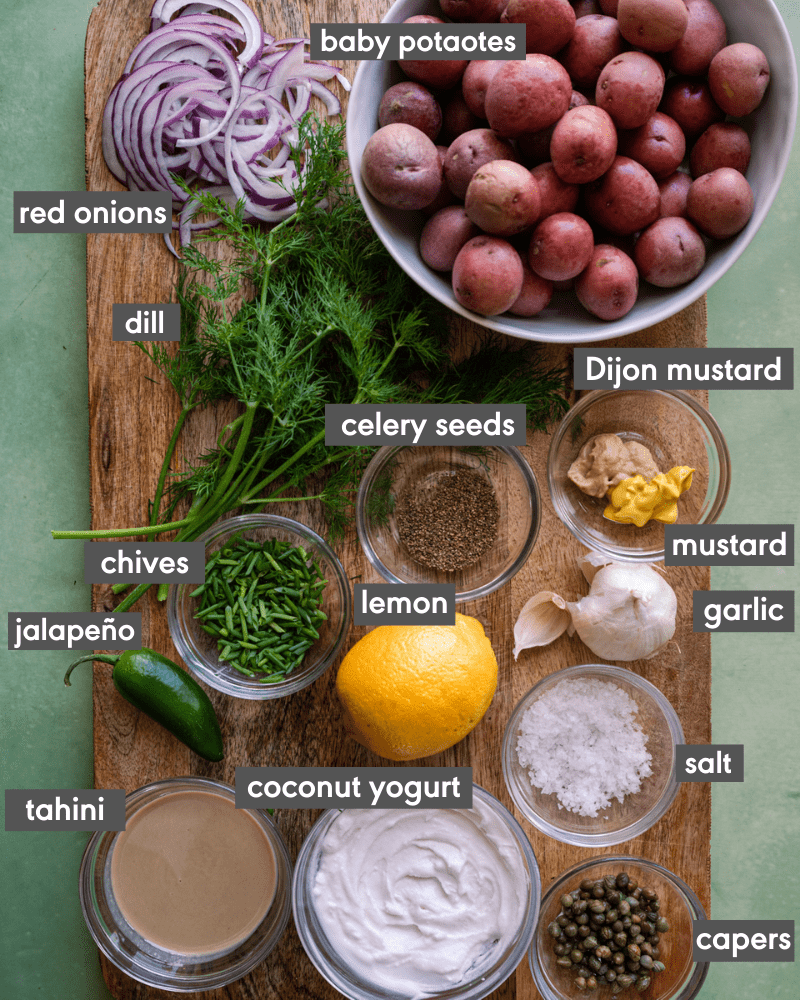 flatlay of ingredients for vegan potato salad with ingredients labeled