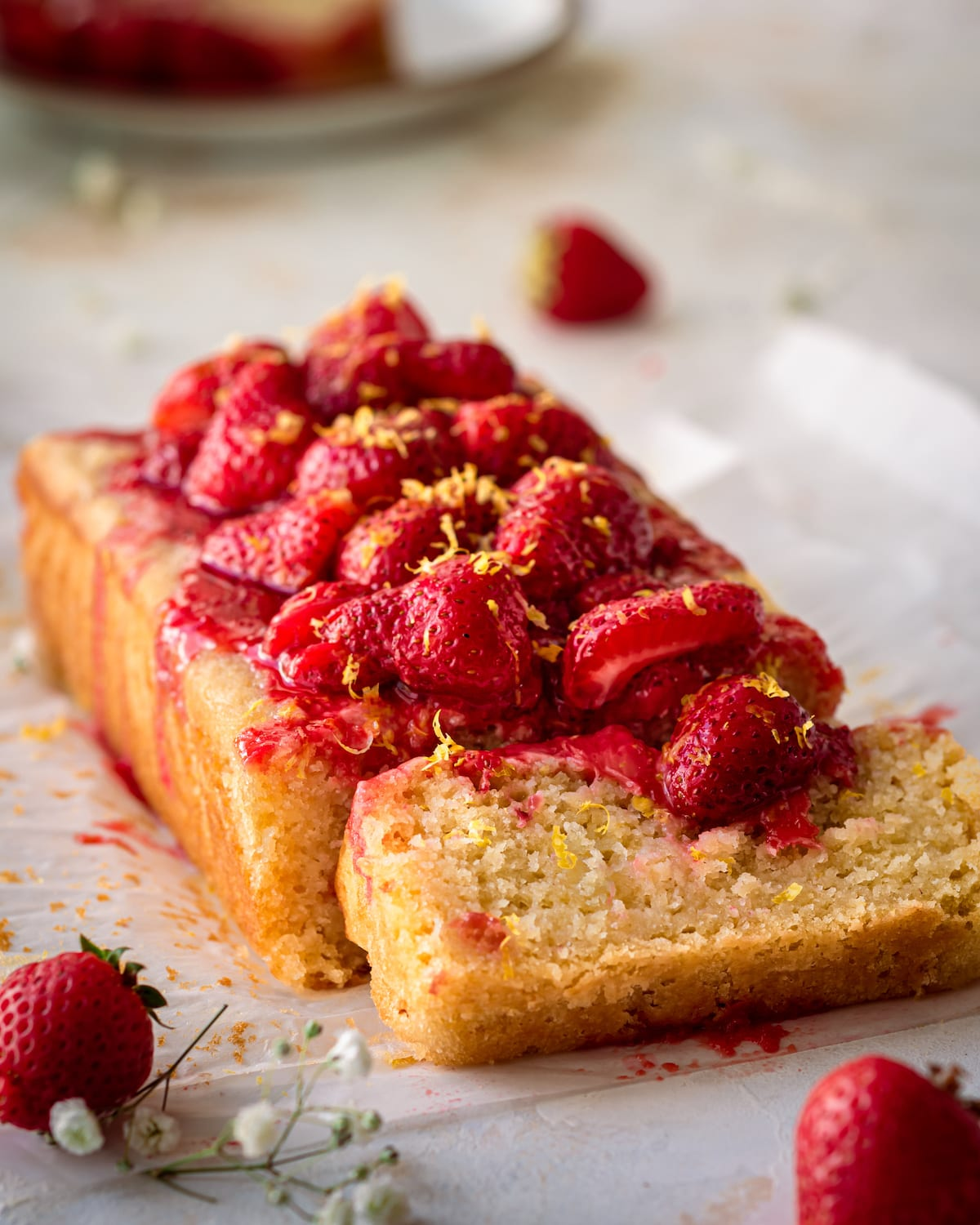 lemon olive oil cake on parchment paper with strawberry sauce on top