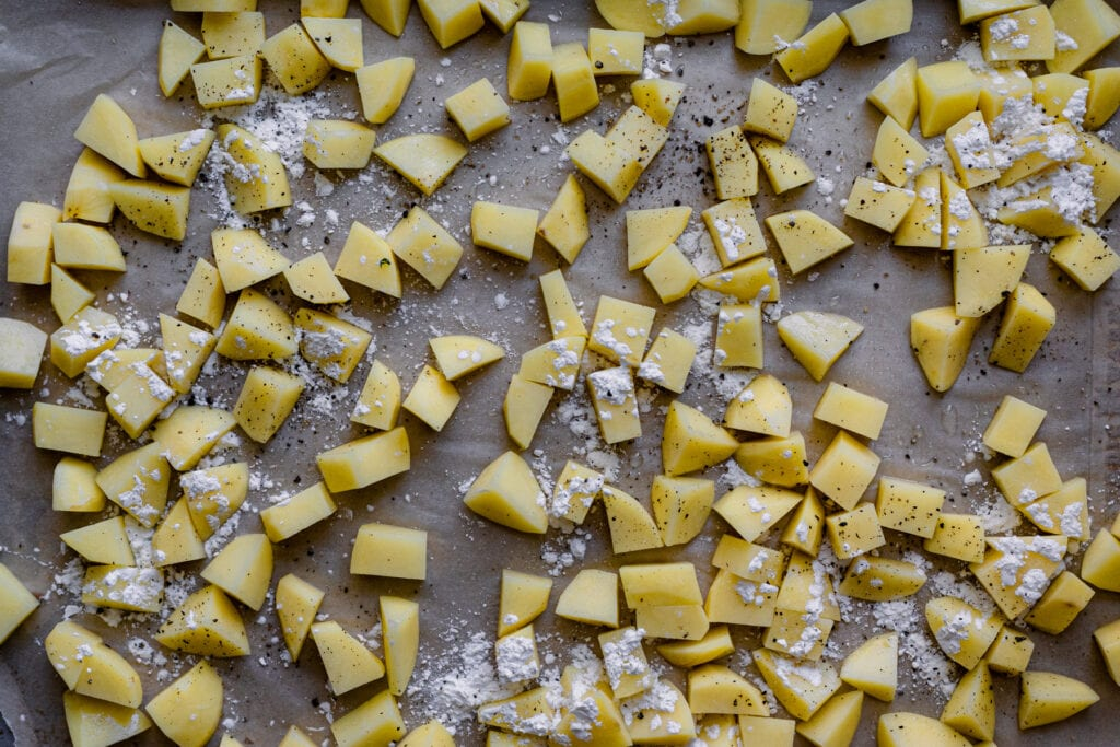 peeled and diced potatoes with cornstarch on baking sheet