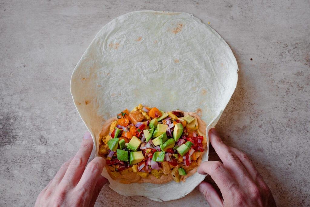 man's hands rolling up a vegan breakfast burrito