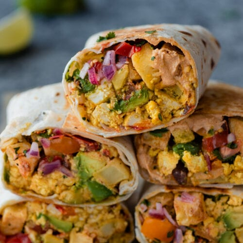 a closeup photo of a stack of vegan breakfast burritos on a blue backdrop