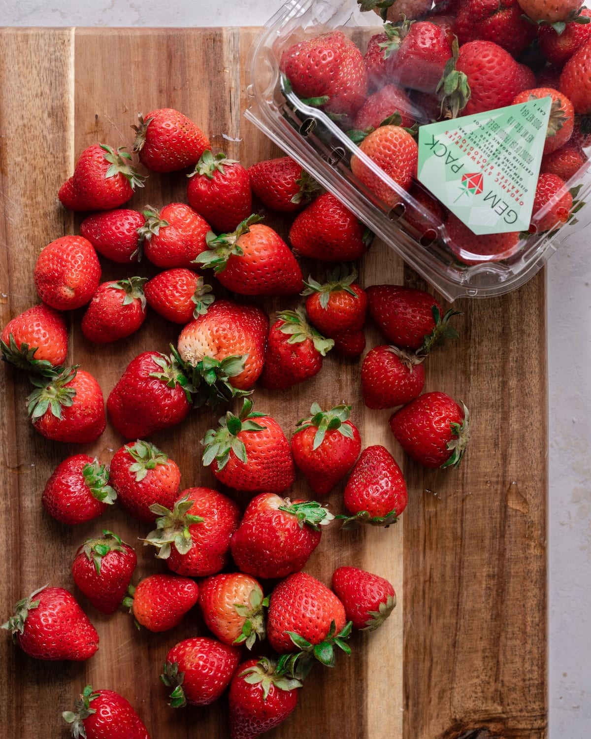 whole strawberries on wooden cutting board with package of strawberries